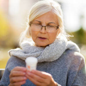 grey haired woman examines pill bottle lable
